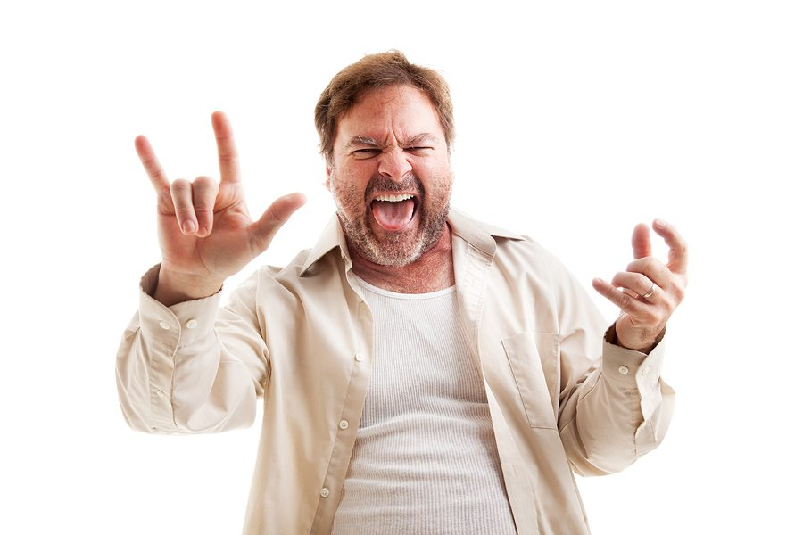 Middle-aged man rocks out playing air guitar and making the rock