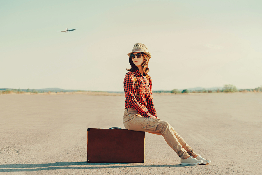 Traveler Woman Sitting On Suitcase On Road
